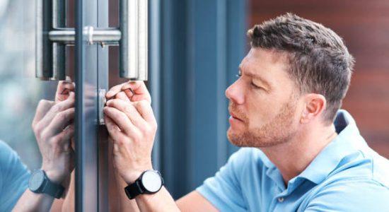 Serrurier qui installe une serrure sur une porte-fenêtre