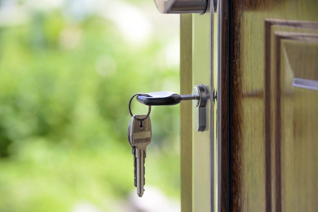 Porte d'entrée d'une maison ouverte avec les clés dans la serrure