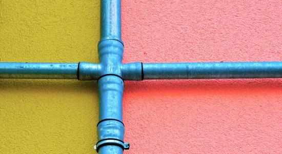 Deux tuyaus bleus se croisant sur un mur coloré